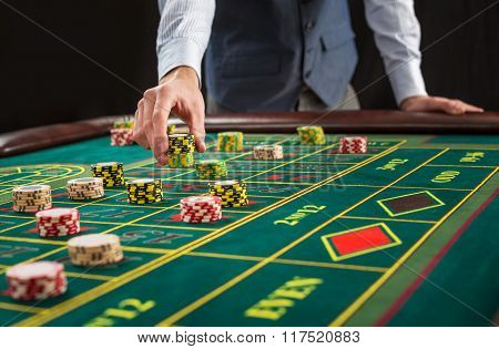 Picture of a green table and betting with chips.