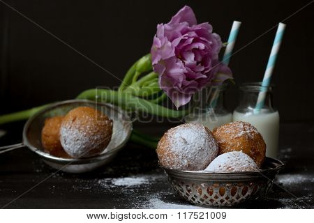 Jelly doughnuts, pink tulip and two bottles of milk