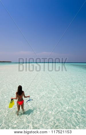 Woman with snorkeling gear looking at the sea