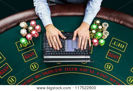 Closeup of poker player with playing cards, laptop and chips