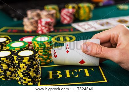 Male poker player lifting the corners of two cards aces