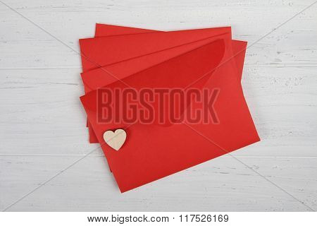 Red paper envelopes with hearts on white wooden background