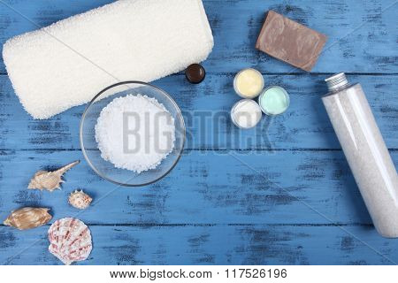 Aromatherapy spa set with natural soap, bath salt and towel on blue wooden background