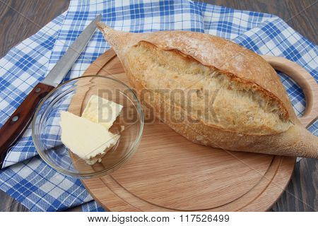 Homemade baked wheaten bread and butter on blue towel