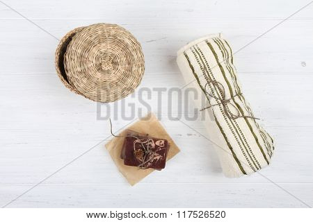 Natural soap and towel on white wooden background