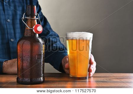 Closeup of a man with a glass of beer and an old fashioned swing top beer bottle. Horizontal format with copy space.