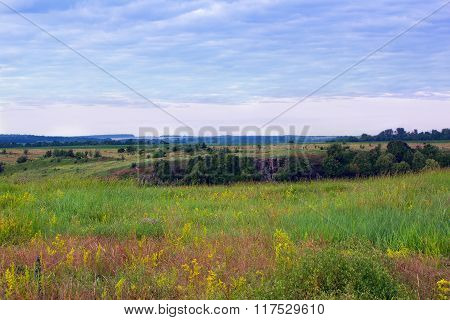 Landscape Of Grassy Valley, Hills With Trees And Cloudy Sky