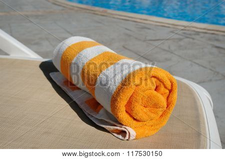 Yellow Towel Lying On A Lounger Beside The Swimming Pool