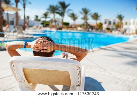 Happy Woman Lying On A Lounger By The Pool At The Hotel