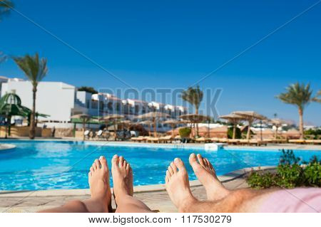 Man And Woman Sunbathing By The Pool At The Hotel