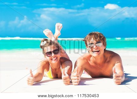 happy young couple lying at a tropical beach. thumbs up. gesture