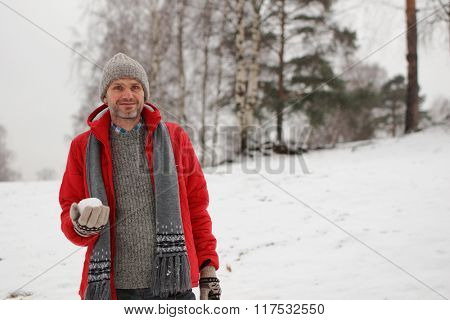 Mature man with snowball during snowball fight