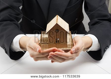 Hands holding small model of house. Real estate concept