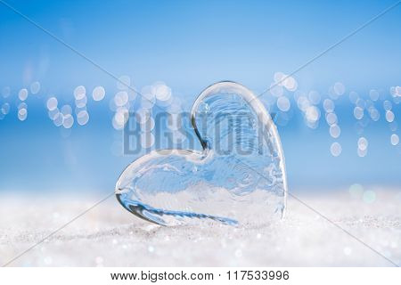 clear glass heart on white  glitter and blue abstract background