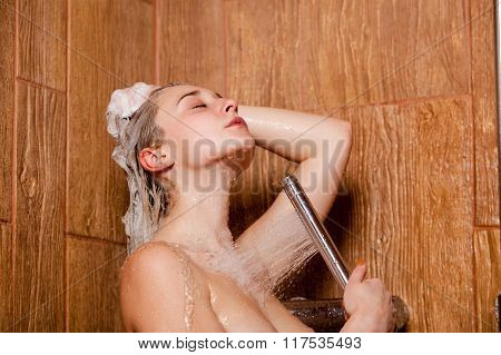 Beautiful woman standing at the shower.  She holds in her hand showerhead