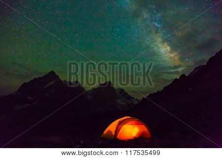 Night mountain landscape with illuminated tent