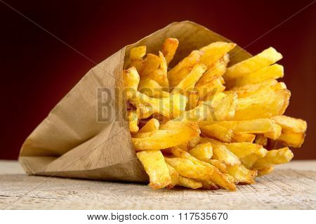 French Fries In The Paper Bag On Burned Background On Wooden Table