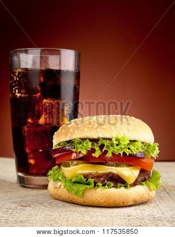 Big Cheeseburger With Glass Of Cola On Wooden Table
