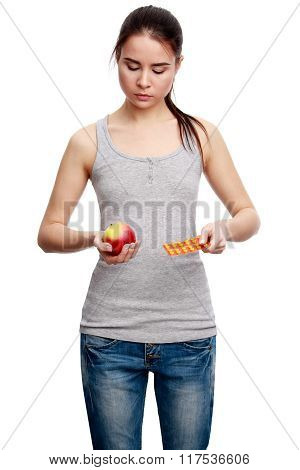 Young Serious Woman Holding A Pill In One Hand And An Apple In The Other