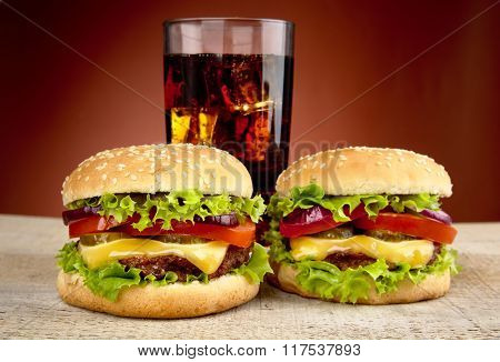 Two Cheeseburgers,glass Of Cola On Wooden Table On Red Spotlight