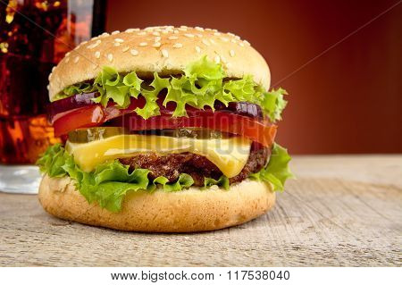 Big Cheeseburger With Glass Of Cola On Red Spotlight