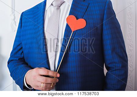 Red heart on a stick in a man's hands.