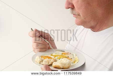 Man having fried eggs and biscuit with copy space