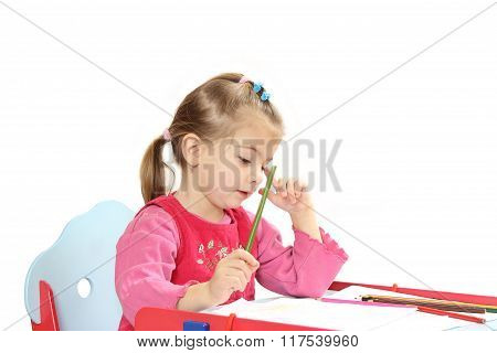 The Little Girl Sitting At A Table Draws Pencils