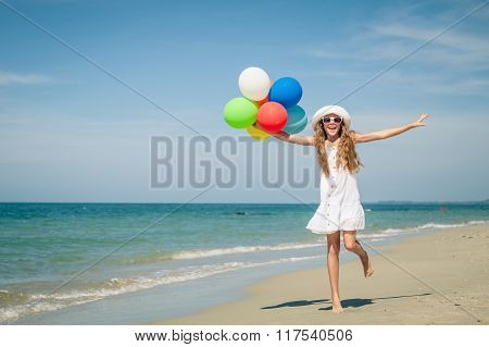 Teen Girl With Balloons Jumping On The Beach