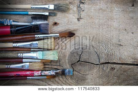 Set Of Old Messy Paintbrushes On A Wooden Background
