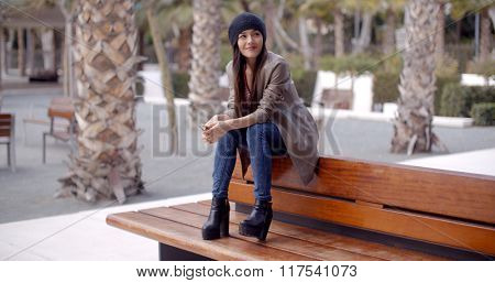 Fashionable young woman sitting waiting on a bench