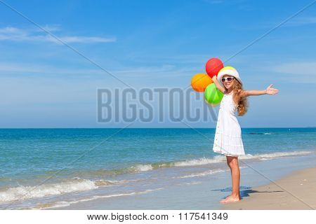 Teen Girl With Balloons Standing On The Beach