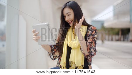 Excited woman waving at her tablet computer