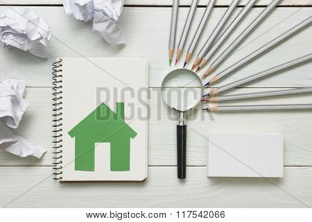 Real estate concept - magnifying glass, pencils and blank business card on wooden table. Copy space