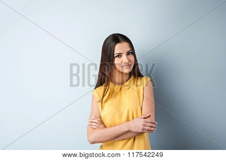Photo of beautiful young business woman standing near gray background. Woman with yellow shirt looking at camera