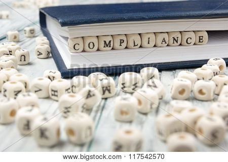 Compliance word written on wood block.