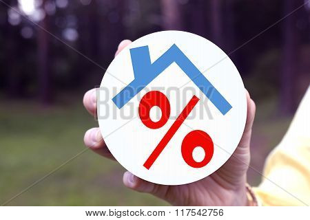 Red percent under the roof in a woman's hand