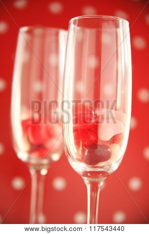 Heart candies in wine flutes against polka dots