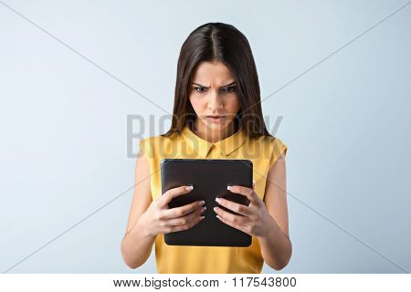 Photo of beautiful young business woman standing near gray background. Angry woman with yellow shirt using tablet computer