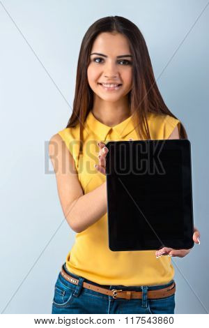 Photo of beautiful young business woman standing near gray background. Smiling woman with yellow shirt showing tablet computer and looking at camera