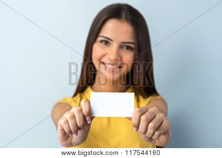 Photo of beautiful young business woman standing near gray background. Woman with yellow shirt looking at camera, smiling and showing visit card. Focus on visit card