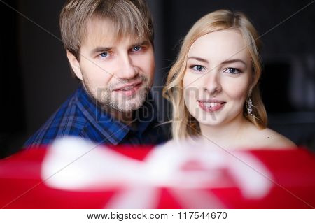young couple presenting a gift to someone