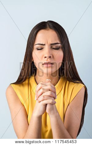 Photo of beautiful young business woman standing near gray background. Woman with eyes closed praying