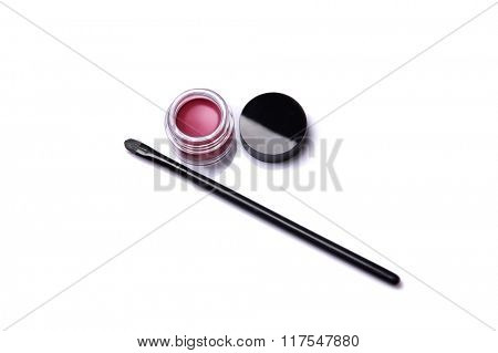 Red lip gloss in jar with makeup brush, isolated on white background with natural reflection