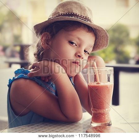Clever Serious Kid Girl Drinking Vitamin Smoothie Juice In Street Cafe And Looking. Toned Closeup Po