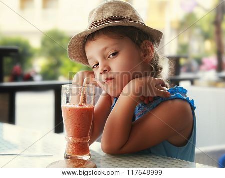 Clever Serious Kid Girl Drinking Vitamin Smoothie Juice In Street Cafe And Looking