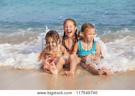 Three Happy Children  Playing On The Beach