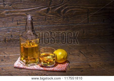Bottle With A Glass With Whiskey And Lemon Are On The Napkin