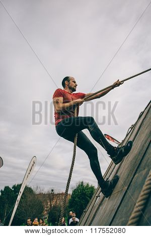 Runner climbing wall with a rope in test of extreme obstacle race