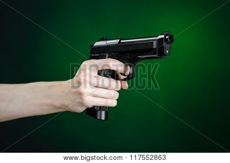 Firearms And Murderer Topic: Human Hand Holding A Gun On A Dark Green Background Isolated In Studio